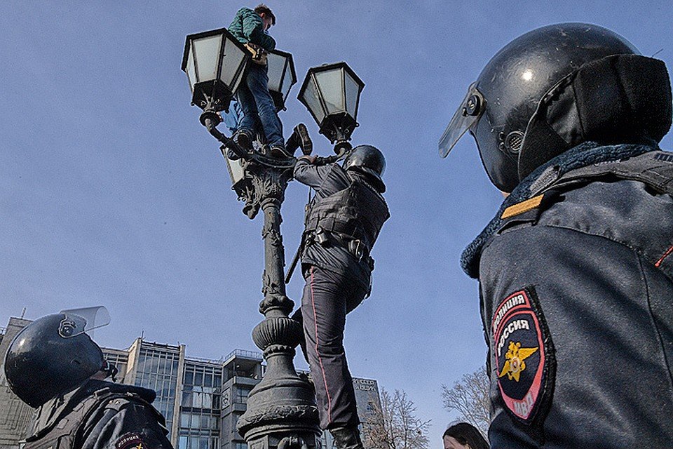 26 марта 2017 года, Москва. Полицейский пытается стащить участника несанкционированного митинга с фонаря на Пушкинской площади.