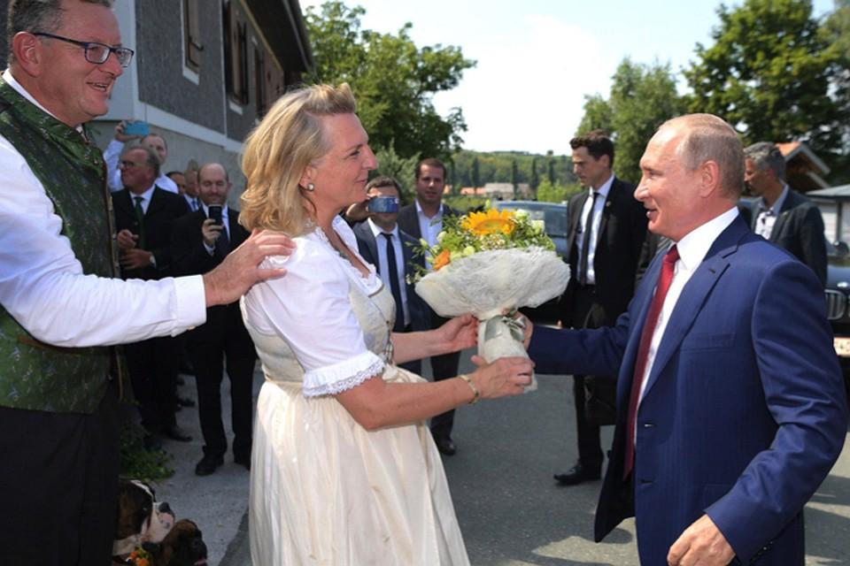 По прибытии президент РФ вручил Карин Кнайсль букет цветов