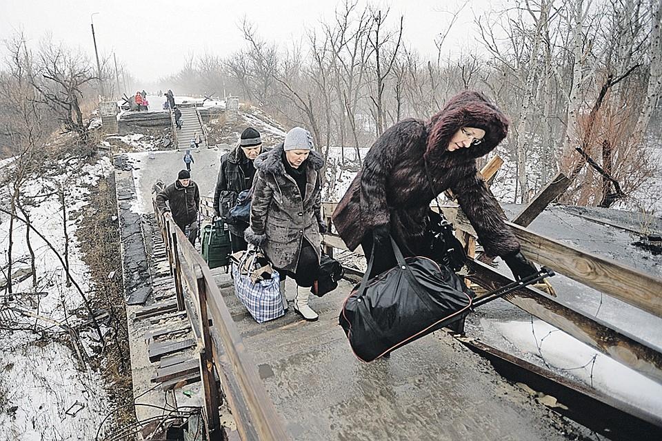 Этот мост между Украиной и Новороссией взорвали во время боев 2014-го.  Да так и оставили.  Люди туда и обратно карабкаются, какальпинисты.