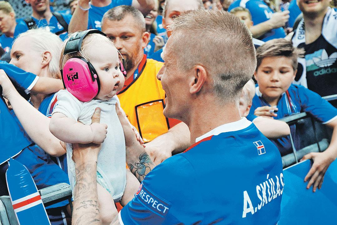 Главную сенсацию на Евро сотворила Исландия, которая пробилась в 1/8 финала со второго места в группе F, опередив португальцев. На фото - исландский защитник Ари Скуласон со своим сыном празднует победу над австрийцами (2:1). Фото: Darren Staples/REUTERS
