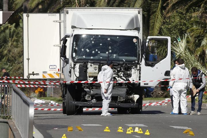 Полицейские работают возле грузовика, врезавшегося в толпу отдыхающих в Ницце
