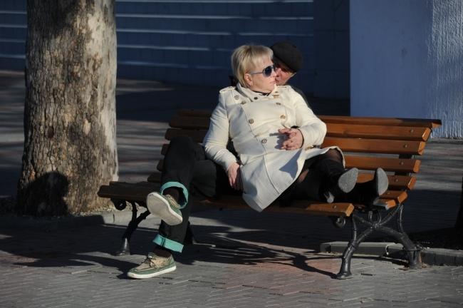Муж и жена отдыхают на скамейке.