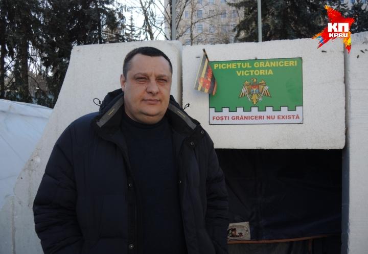 """Протестующий Олег на фоне плаката """"Пограничники бывшими не бывают"""" Фото: Дарья АСЛАМОВА"""