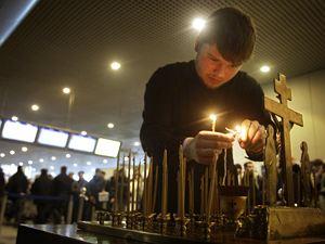 В зале прилета на месте гибели людей пассажиры зажигают свечи... Фото: АП