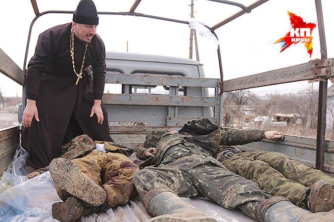Священник грузит тела украинских воинов. Фото: Александр КОЦ, Дмитрий СТЕШИН