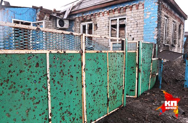 Еще одно чудо — уходящий за горизонт ряд измочаленных домов, и вдруг — уцелевшая хатенка, выкрашенная в веселый зеленый и синий. Фото: Александр КОЦ, Дмитрий СТЕШИН