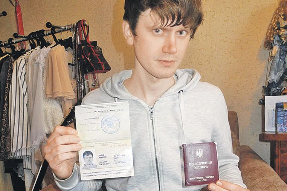 Алексей Белаш, украинский разведчик, перешел на сторону «врага». В левой руке у него - военный билет, в правой - удостоверение беженца.