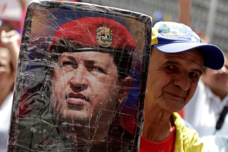 Сторонник президента Мадуро с портретом его предшественника - Уго Чавеса.
