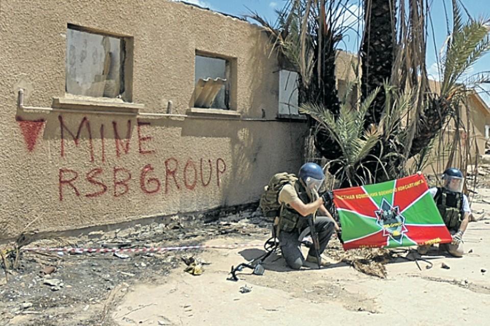 Бойцы «РСБ-Групп» развернули флаг ЧВК на фоне разминированного ими здания цементного завода в Бенгази (Ливия). Фото: ЧВК «РСБ-Групп»