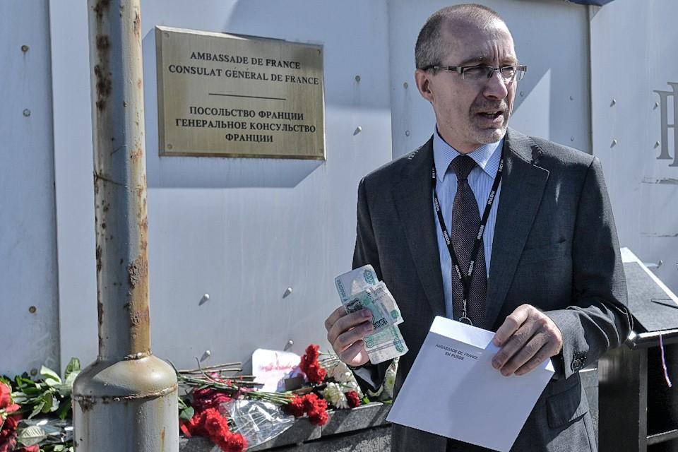 К стенам посольства Франции в Москве неравнодушные несут цветы, рисунки и... пожертвования на восстановление собора.