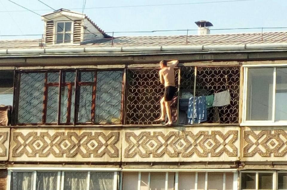 """Суровый сибиряк по балконам залез на крышу многоэтажки и улегся загорать. Фото: группа """"Непростой Ангарск"""" ВКонтакте"""