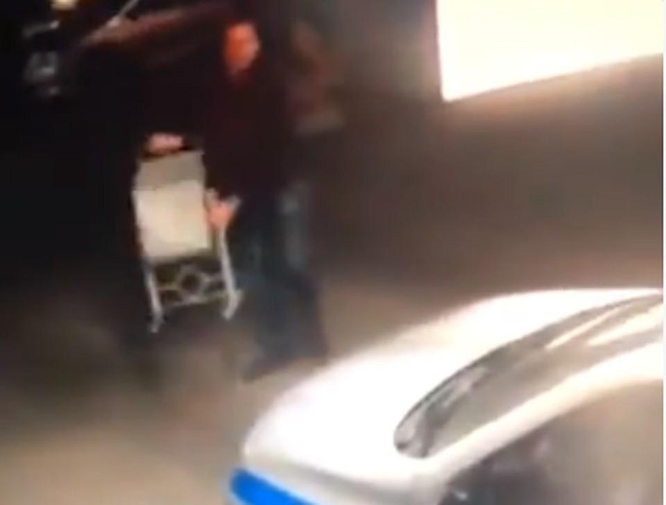На одной из парковок разбушевавшийся мужчина запустил в машину полиции урну. Скриншот видео.