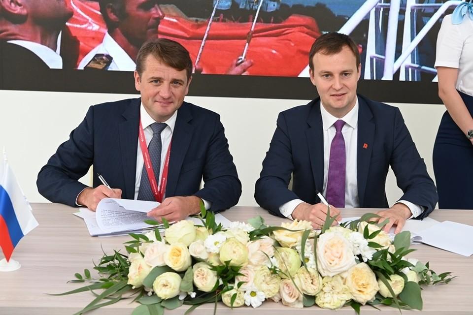Илья Шестаков и Федор Кирсанов подписывают договор. Фото: пресс-служба Росрыболовства