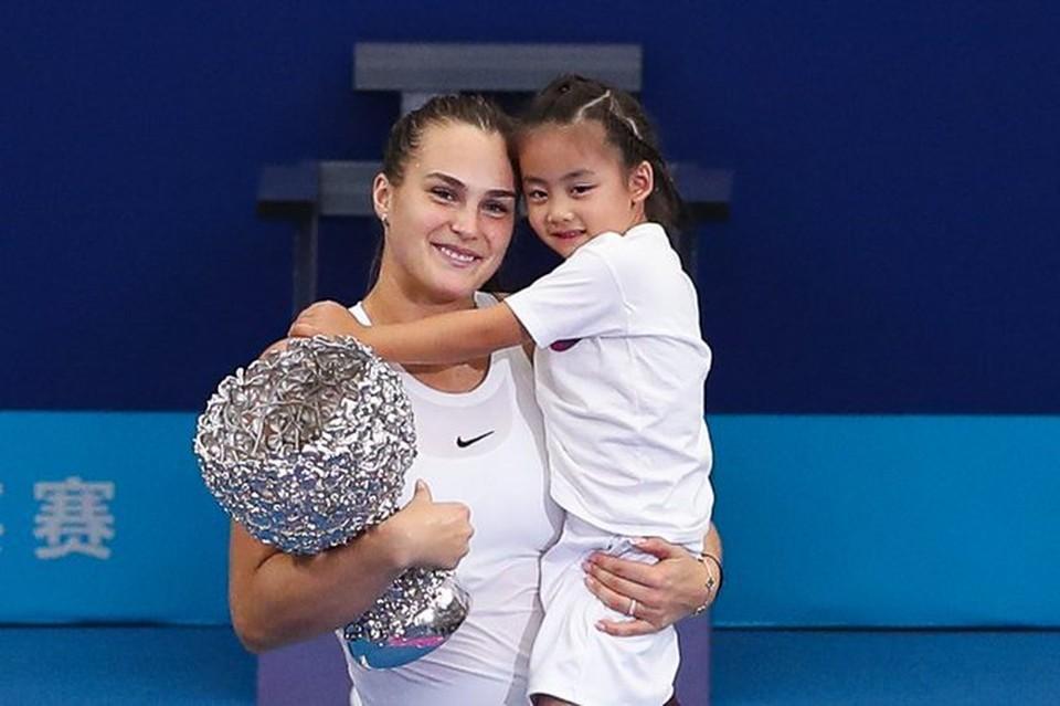 Арина Соболенко с маленькой китаянкой и трофеем малого Итогового турнира WTA. Фото: twitter.com/WTAEliteTrophy