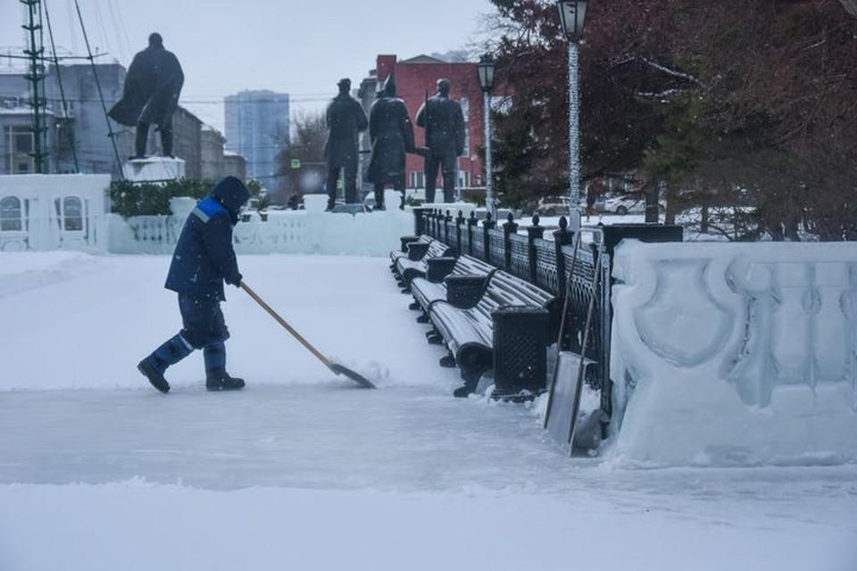 Рвботники активно расчищают каток от снега.