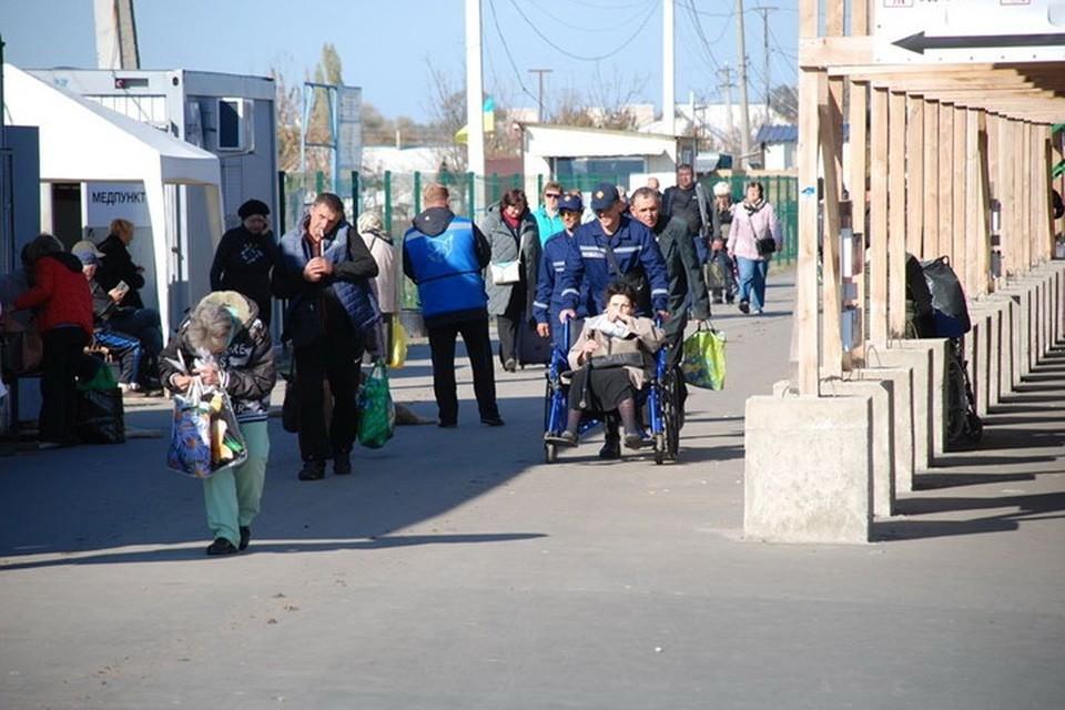 В Станице Луганской часто можно увидеть пенсионеров-инвалидов из ЛНР, которых на колясках добровольцы доставляют к пунктам выплаты пенсий. Фото: Фейсбук/Евгений Каплин