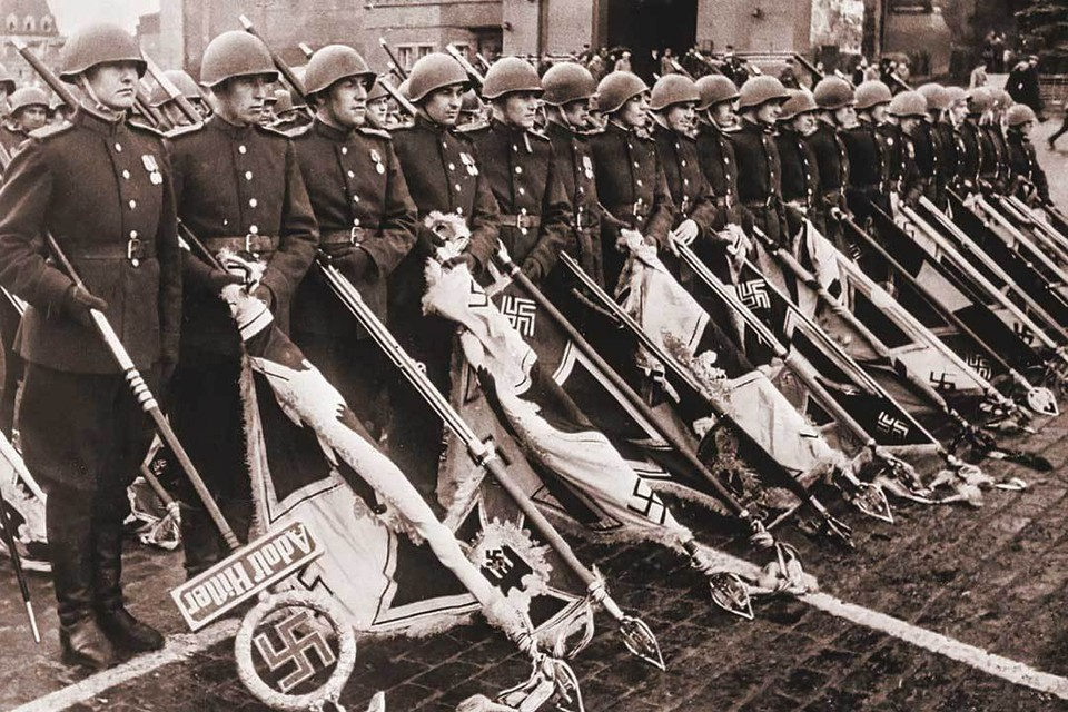 24 июня 1945 года. Первый Парад Победы. По предложению Сталина он завершался складированием флагов поверженных гитлеровских войск к подножию Мавзолея. Знамена и штандарты врага пронес сводный батальон из 200 советских солдат. Идея «публичной казни» вражеских знамен была заимствована у великого полководца Александра Суворова, в войсках которого был ритуал «небрежения не к неприятелю, а к его поверженным военным отличиям». Слева на фото - сержант Федор Легкошкур с древком штандарта дивизии СС «Адольф Гитлер», он первым с презрением швырнул фашистское древко на мокрый асфальт. Само полотнище штандарта было привезено в Москву из Берлина уже после Парада.