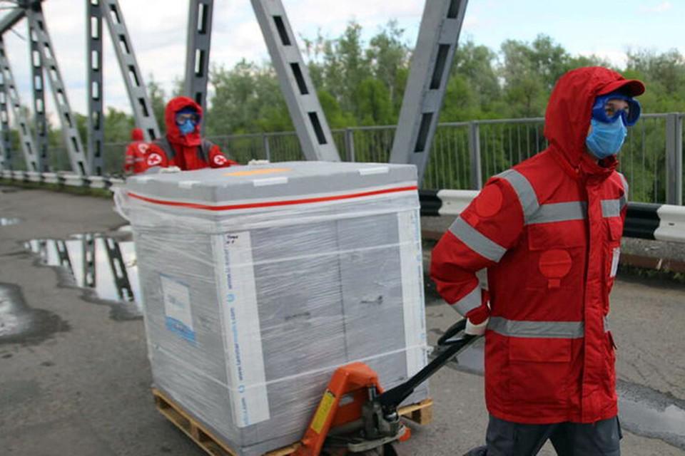 Сотрудники Красного Креста для перевозки груза по мосту используют гидравлические погрузочные тележки. Фото: МККК