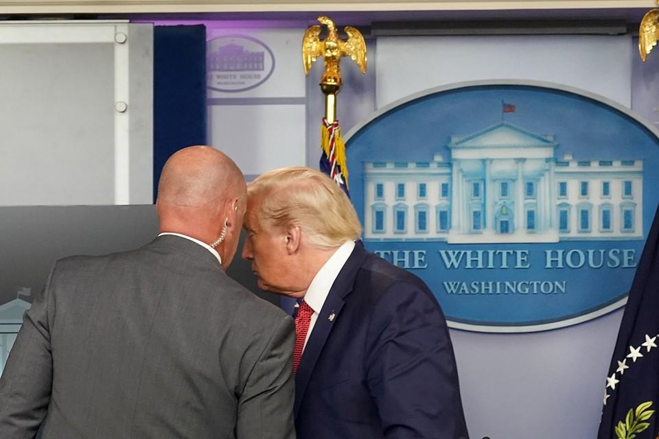 K Дональду Трампу подошел сотрудник секретных служб и что-то прошептал ему на ухо, а затем быстро вывел его из зала