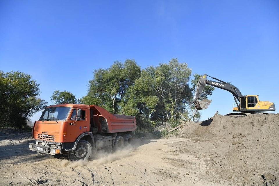 Огромный экскаватор на берегу Терека черпает грунт из русла реки.