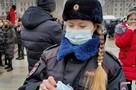 Сотрудница полиции раздает маски участникам несанкционированной акции в центре Москвы