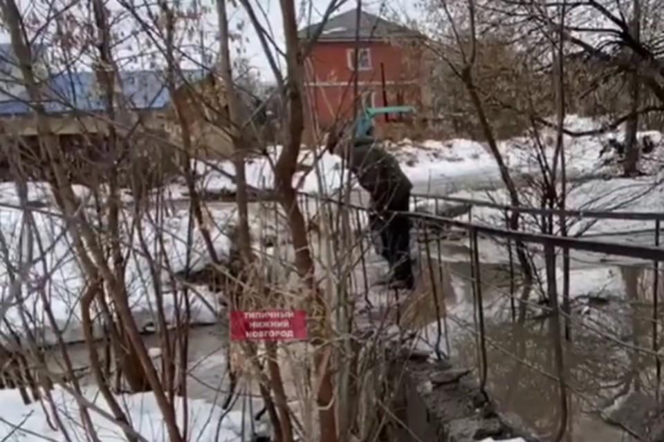 Пешеходы с трудом преодолевают затопленный мост через реку Старку. Фото: Типичный Нижний Новгород