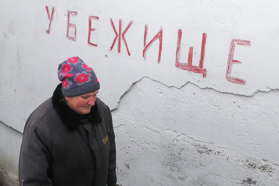Женщина у бомбоубежища в городе Ясиноватая, Донецкая область. Фото: Валентин Спринчак/ТАСС