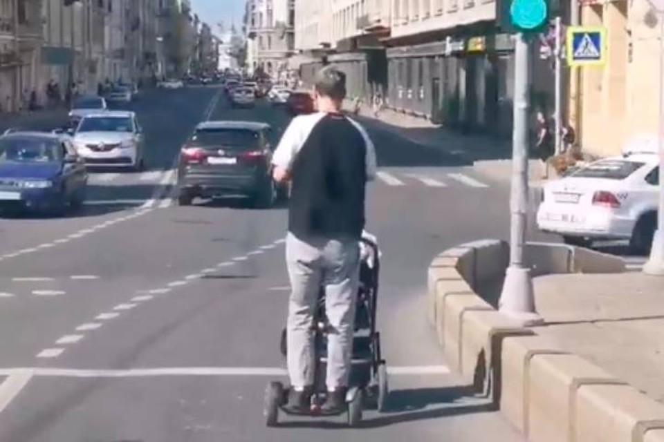 Современный отец на гироскутере с детской коляской проехал по проезжей части в центре Петербурга
