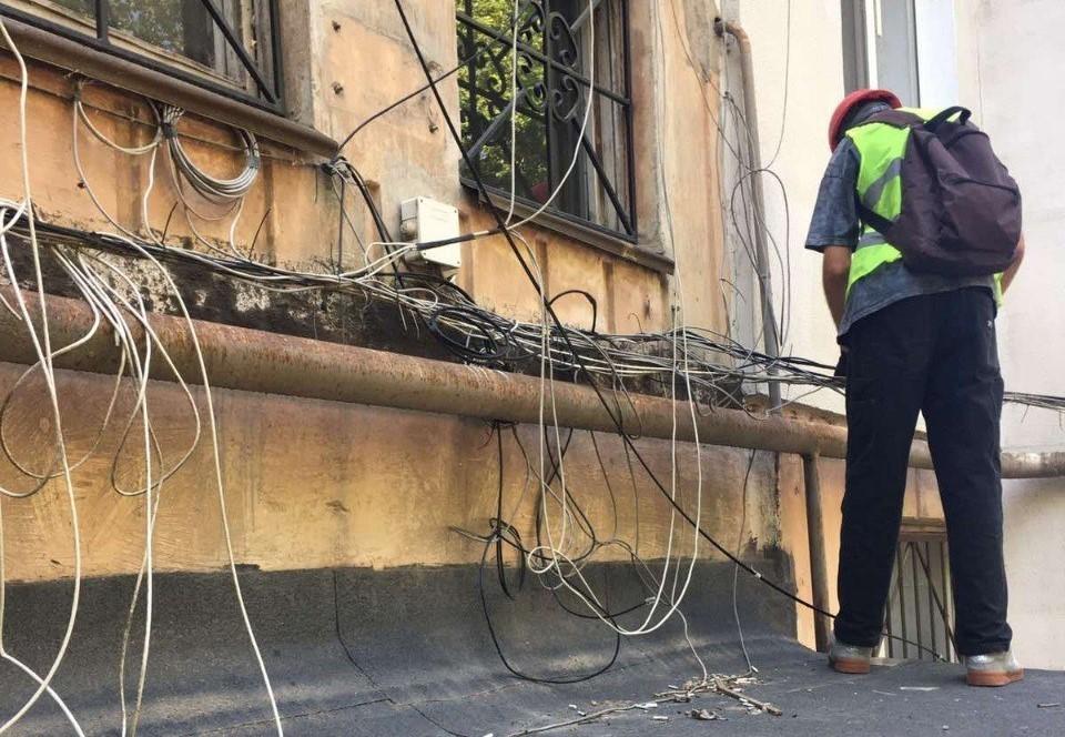 """Рабочие приводят в порядок """"скопище"""" проводов, которые портят внешний вид строений. Фото: пресс-служба администрации Симферополя"""