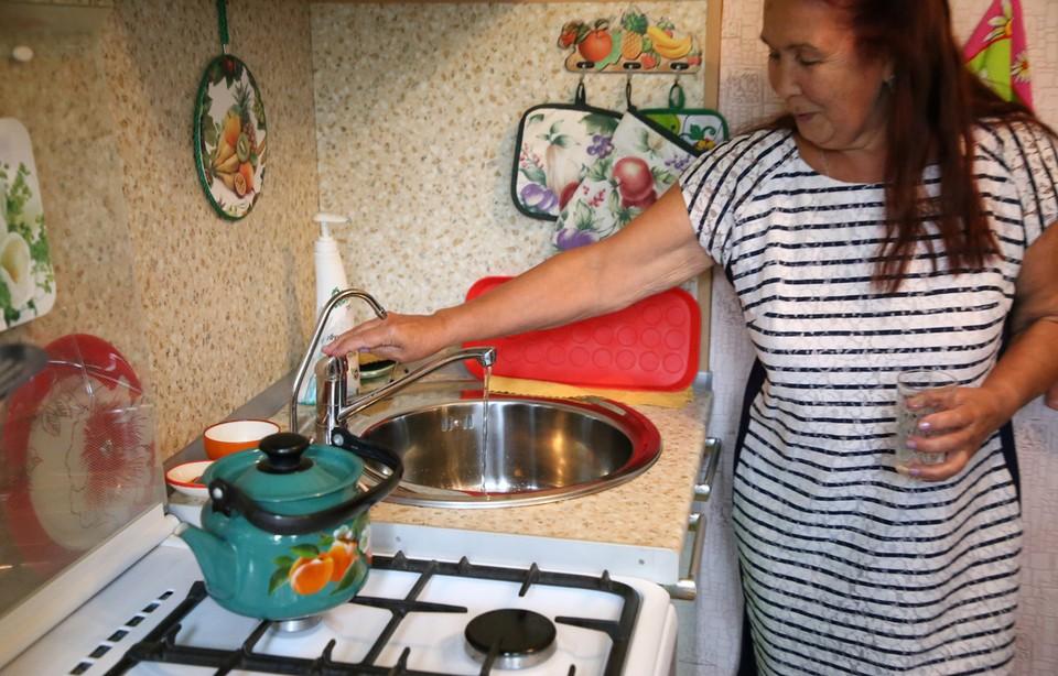 Пенсионерка Лариса Копылова показывает, что вода теперь у неё из крана в квартире во Ржеве течёт чистая.