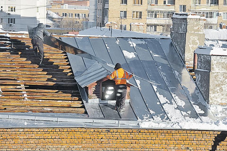 Рабочие чинят крышу без всякой страховки.