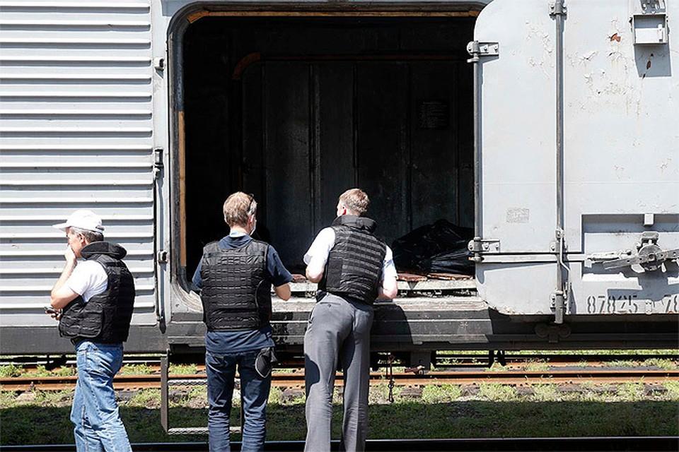 """Специалисты ОБСЕ осматривают вагон-рефрижератор с телами погибших в крушении """"Боинга"""" Малайзийских авиалиний."""