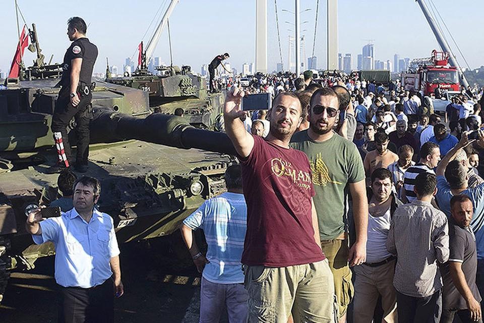 Жители Стамбула фотографируются у моста, который еще несколько часов назад занимали военные.