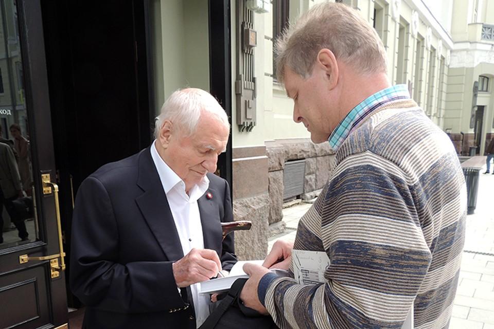 Марк Захаров раздает автографы поклонникам перед входом в театр