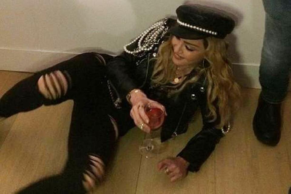 Мадонна опустилась на пол и расположилась с бокалом под собственным портретом. Фото: Инстаграм.