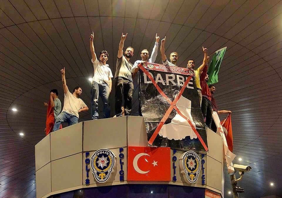 Противники путчистов скандируют на крыше полицейского участка в здании аэропорта Ататюрк.