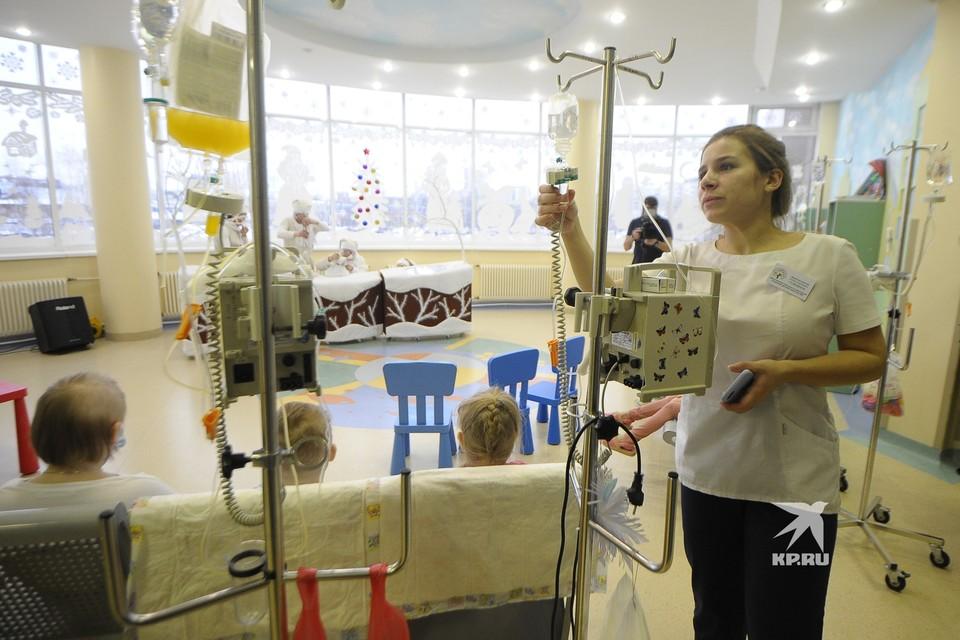 Медсестра проверяет капельницу у детей-пациентов детского онкоцентра, пока те смотря новогодний спектакль театра кукол