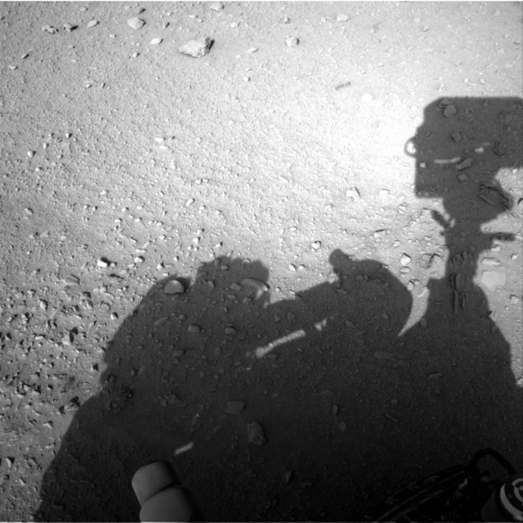 """Тень человека в скафанде пала на поверхность Марса рядом с роботом """"Любопытство""""."""