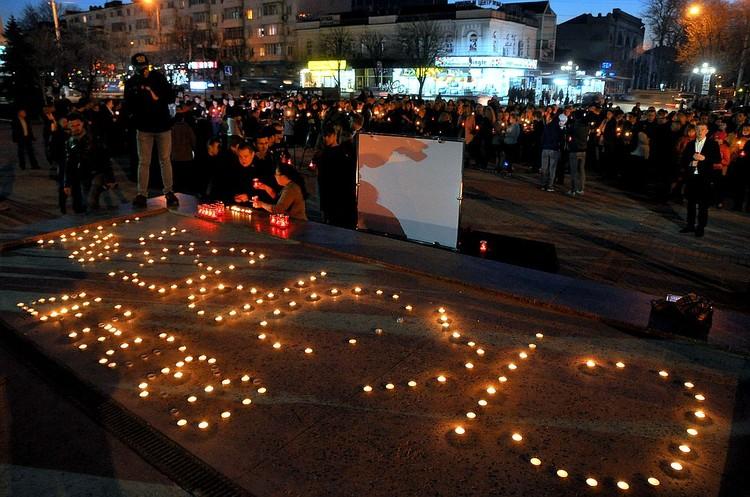 В Центр Симферополя пришли люди. Все они принесли свечи.