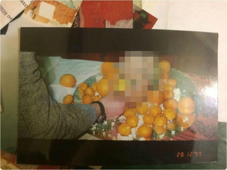 На одной из карточек на усыпанном мандаринами блюде лежит приготовленная голова человека.
