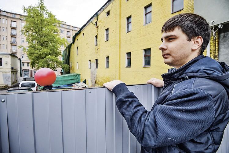 Активист Андрей Новичков забрался на забор, который окружает дом на Остоженке, 4. Двери и окна опечатаны, но именно тут периодически живут бродяги.