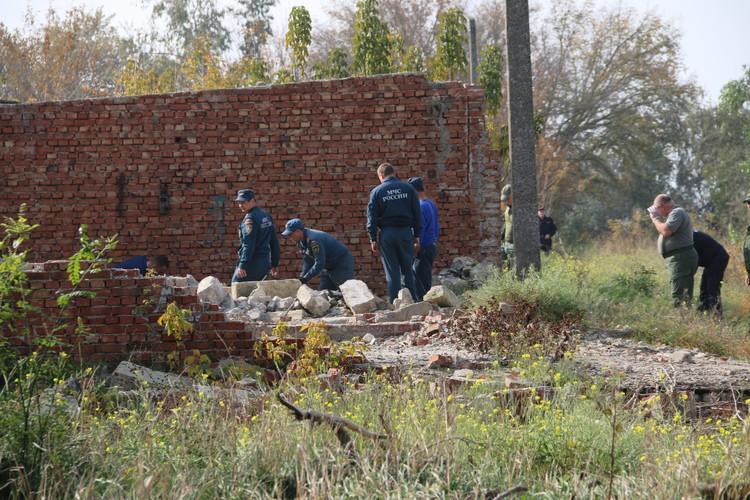 Сотрудники МЧС и СКР исследуют одно из полуразрушенных строений недалеко от дома стрелка