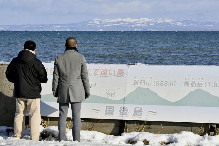 Японские туристы смотрят с территории острова Хоккайдо на российский остров Кунашир, входящий в южные Курилы.