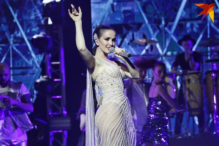 Она вышла на сцену в длинном блестящем платье.