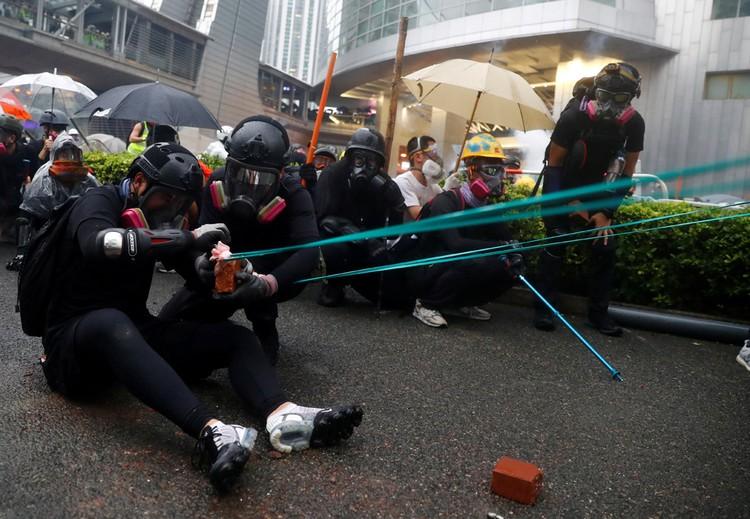Протестующие с помощью рогаток обстреливают полицию.