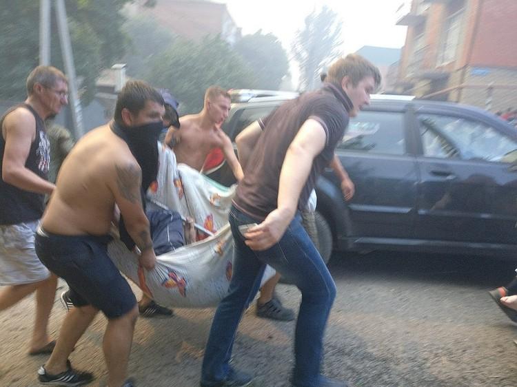 Люди помогают пострадавшим при пожаре