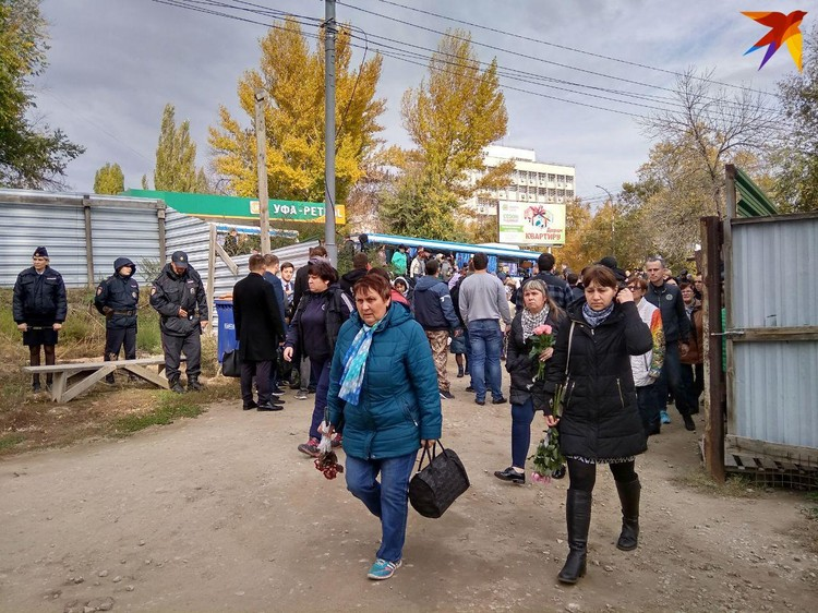 Из подъезжающих автобусов выходят все новые десятки людей с цветами