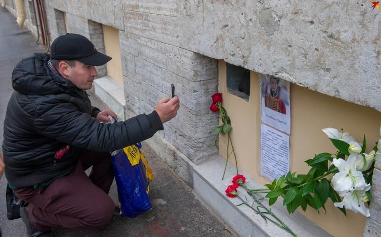 Прохожие останавливаются около самодельного мемориала