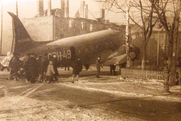 """Самолет Ли-2 с """"отстегнутыми"""" крыльями на улице Молодой Гвардии, движется на погрузку в порт."""