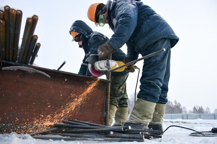Рабочие режут арматуру.
